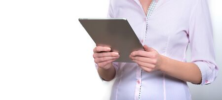 Tablet in the hands of a girl in a shirt. Stand-alone photo. Business photography Banco de Imagens