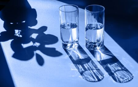 Two glasses of water. Bright light and contrasting shadows. Sun glare. Blue tinting. Trend 2020