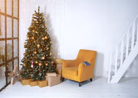 New years interior. Decorated Christmas tree in the interior of the living room. The blue book is on the yellow chair. White walls in the interior.