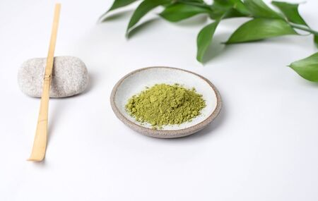 White ceramic spoon with tea of a match on a light gray background. Matcha green tea in powder