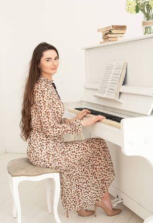 Beautiful young woman with dark long hair at the piano.