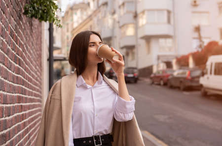 A young woman walks down the street. Drink your morning coffee.