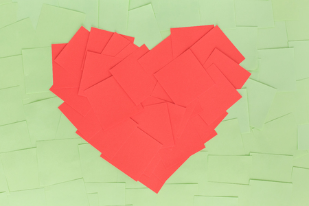 The background of square, paper stickers in the shape of a red heart on a light green background