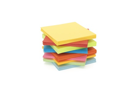 unevenly: a stack of multicolored paper stickers, stacked unevenly on a white background