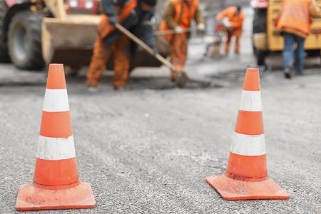wegwerkers het repareren van de weg met schoppen, dub asfalt met schoppen aan de achterkant, de kegels in de voorgrond