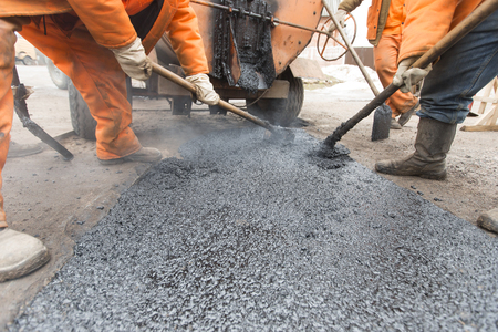 Road workers in bright uniforms lay asphalt, repair the road. Men with shovels and a tool repair section of the road.