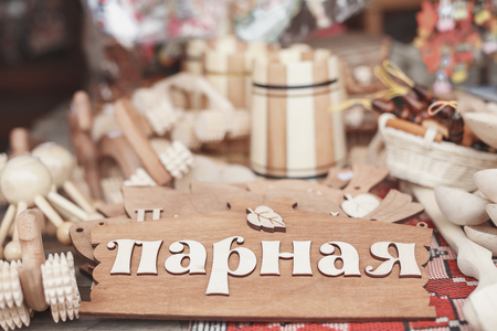 vaporarium: wooden  plate with the inscription steam on the door of the   bathhouse. Around wooden objects, cups, tumblers made of wood. ?ll the items on the table Stock Photo