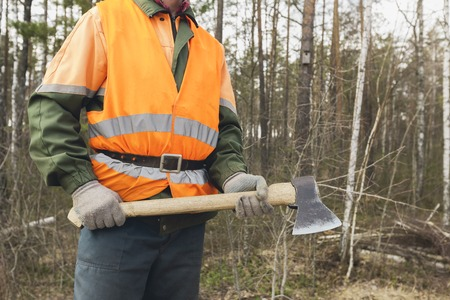 ax man: Lumberjack with an axe in the hands of the forest backdrop. One worker in special clothes in the foreground.