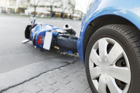 Wypadek niebieski rower z niebieskim samochodem. Motocykl zderzył się zderzaka samochodu na drodze. Motocykl leży na drodze w pobliżu samochodu.