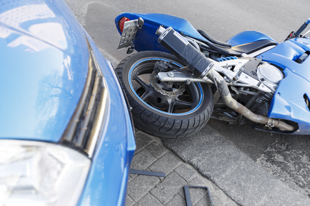 The accident blue bike with a blue car. The motorcycle crashed into the bumper of the car on the road. The motorcycle lies on the road near the car. Stock Photo