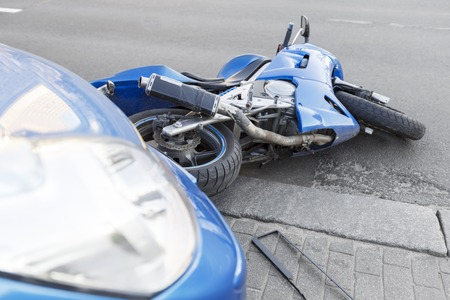 Het ongeval blauwe fiets met een blauwe auto. De motor crashte in de bumper van de auto op de weg. De motor ligt op de weg in de buurt van de auto.