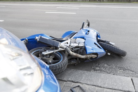 The accident blue bike with a blue car. The motorcycle crashed into the bumper of the car on the road. The motorcycle lies on the road near the car. Imagens