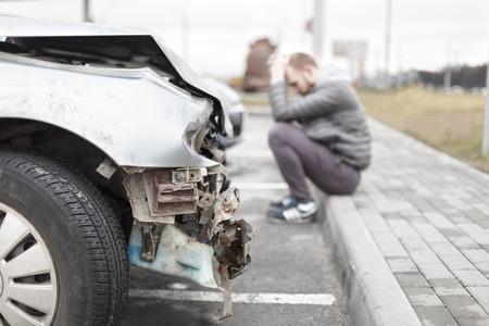 gebroken grijze auto na het ongeval op de voorgrond, gebrokenheid metalen onderdelen, op de achtergrond een man belde de servicedesk Stockfoto
