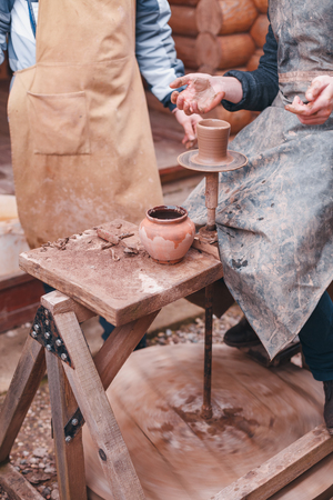 caked: The hands of a potter help make a pitcher on a pottery wheel. Two men with hands caked in clay. One man teaches the second pottery.