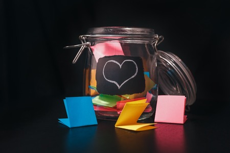 Open Bank with colorful stickers on a black background with white chalk-drawn heart