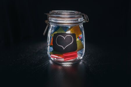 Closed Bank with colorful stickers on a black background drawn with white chalk heart