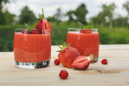 A glass of strawberry smoothie on a wooden table with mint in the garden Stock Photo
