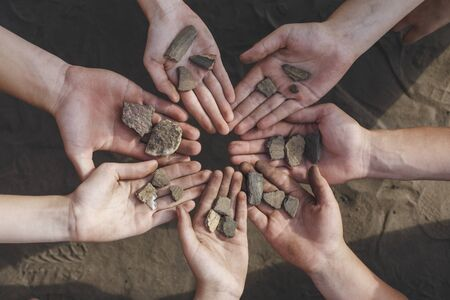 settlements: The children are holding the archaeological finds of stones and the age of seven thousand years ago. Children help in the excavation of human settlements.