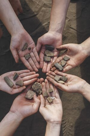 finds: The children are holding the archaeological finds of stones and the age of seven thousand years ago. Children help in the excavation of human settlements.