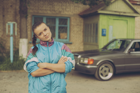 nineties: The girl in the nineties. On the background of old car Stock Photo