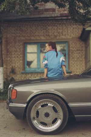 nineties: The girl in the nineties sitting on the hood of the car and inflate the bubble of chewing