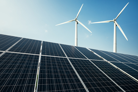 generate: Solar panels and a windmill generate electricity from the sun. Renewable sources of energy. Stock Photo