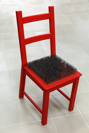 red chair with spikes on the seat. The inability to sit in a chair Stock Photo