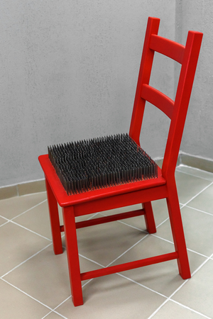 bowel disorder: red chair with spikes on the seat. The inability to sit in a chair Stock Photo