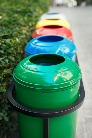 Colored trash containers for garbage separation. Taking care of nature and ecology. The greenery around. Containers for plastic, paper, glass and metal. Stock Photo