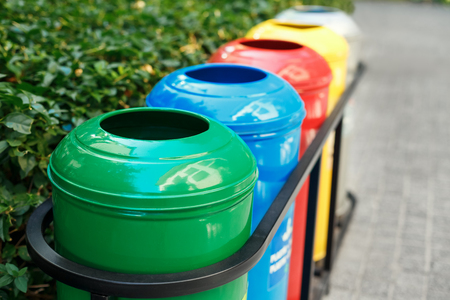 Colored trash containers for garbage separation. Taking care of nature and ecology. The greenery around. Containers for plastic, paper, glass and metal. Archivio Fotografico