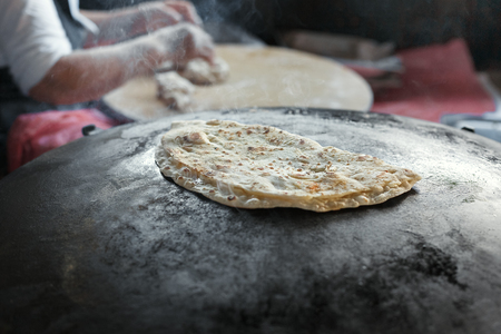 customary: Granny chef cook Turkish pancake Gozleme on the stove. The national dish of Turkish cuisine. Stock Photo