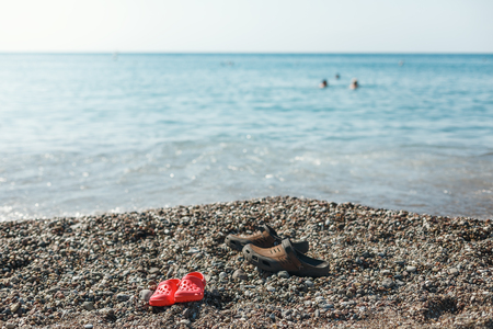 rubbery: shoes childrens and adult stands on the shore of the sea. Stone beach, on the rocks is a rubber shoes Stock Photo