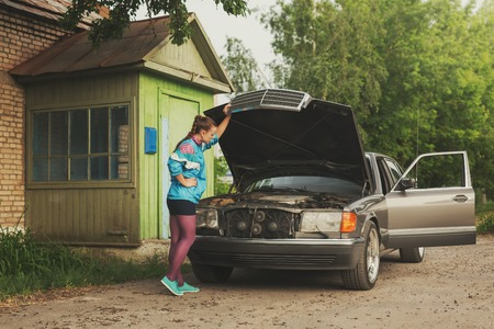 dashing: Girl from nineties of time looking under hood of car Stock Photo