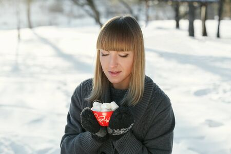 Girl drinks coffee with marshmallows in the winter outdoors. With red circles and looking at the camera. On the mug is written in the sun