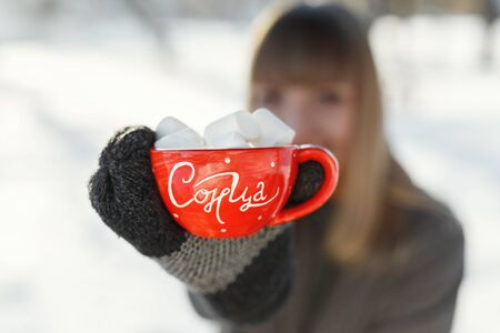 The girl shows with a mug of coffee and marshmallows at the camera. On the mug is written in the sun