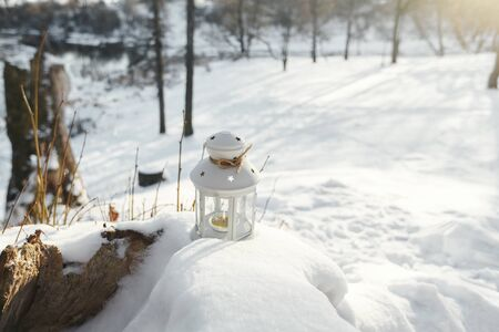 Flashlight inside a burning candle standing in the snow in the winter. Sunset, the sun shines around cold winter Stock Photo