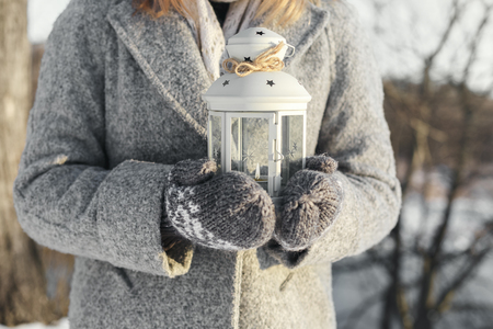 girl holding a lantern with a burning candle inside. Winter, the setting sun shines