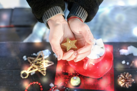 The girl holding a burning candle in the shape of a star. Preparing for the new year and Christmas