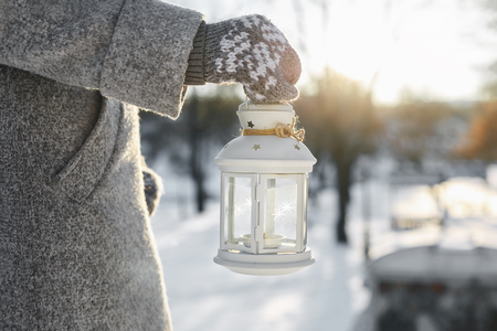 the girl carries a lantern with a burning candle inside. Winter, the setting sun shines Stock Photo