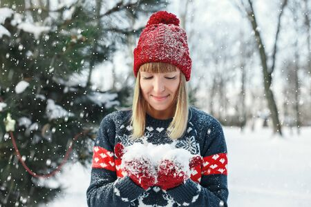 Girl holding snow on mittens and looks at him. Make a wish before the new year. Something wants.