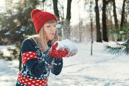 Girl blows snow with mittens and makes a wish. Winter Sunny day Stock Photo