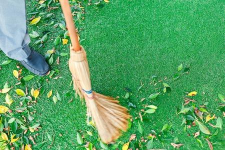 Werken met bezem veegt grasveld van afgevallen bladeren
