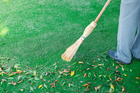 Working with broom sweeps lawn from fallen leaves