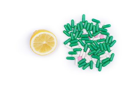 Lemon and pile of pills on white background