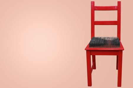 red chair with spikes on the seat