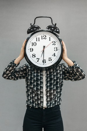 The girl holding a very large alarm clock