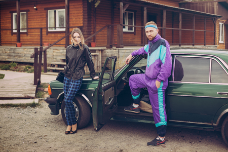 Guy and girl in clothes of the nineties, next to the old car Stock Photo