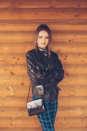 girl in clothes of the nineties, on the background of wooden wall
