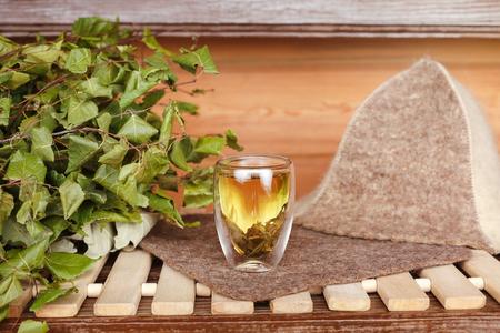 Green tea in glass Cup in the bath near the bath broom Stock Photo