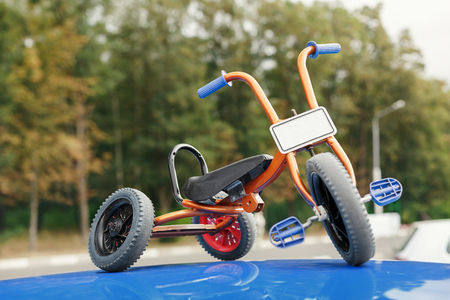 stylish and unusual tricycle on the roof of the car Stock Photo